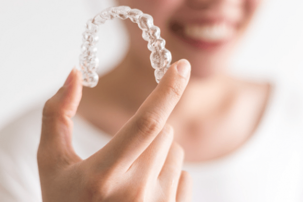 A-Smiling-Woman-Holding-Invisalign-Or-Invisible-Braces-Orthodontic-Equipment